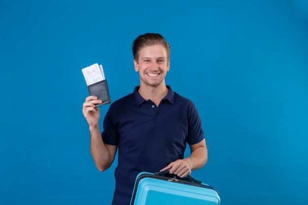 Homem jovem viajante bonito segurando bilhetes de avião feliz e positivo, olhando para a câmera com um grande sorriso no rosto em pé sobre fundo azul