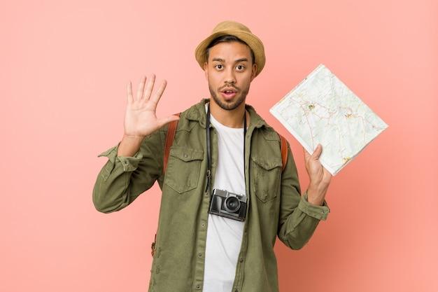 Homem jovem viajante bonito segurando um mapa