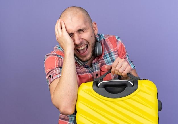 Homem jovem viajante caucasiano dolorido com fones de ouvido no pescoço, colocando a mão na cabeça e segurando uma mala isolada em um fundo roxo com espaço de cópia