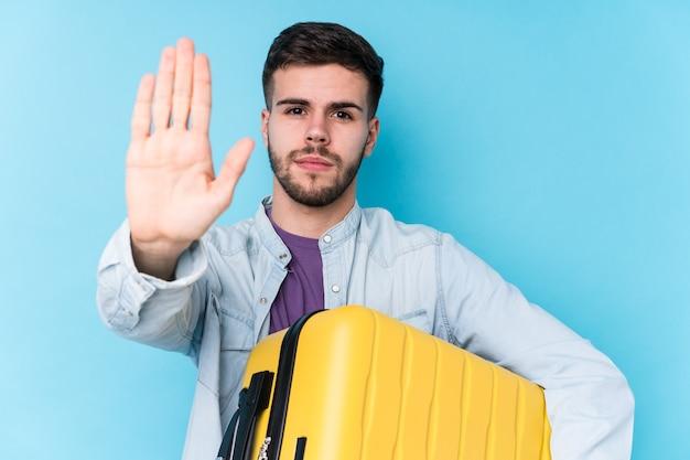 Homem jovem viajante caucasiano segurando uma mala isolada em pé com a mão estendida, mostrando o sinal de stop, impedindo você.