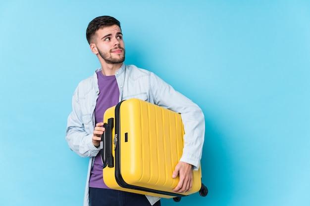 Homem jovem viajante caucasiano segurando uma mala isolada, sonhando em alcançar objetivos e propósitos