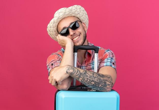 Homem jovem viajante caucasiano sorridente com chapéu de praia de palha em óculos de sol, colocando as mãos na mala isolada em um fundo rosa com espaço de cópia