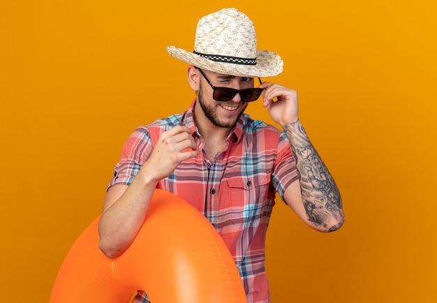 Homem jovem viajante caucasiano sorridente com chapéu de praia de palha em óculos de sol pisca os olhos e segura anel de natação isolado na parede laranja com espaço de cópia