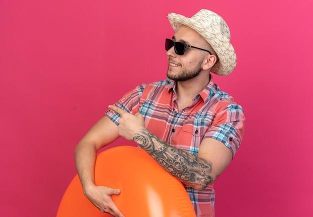 Homem jovem viajante caucasiano sorridente com chapéu de praia de palha em óculos de sol segurando anel de natação olhando e apontando para o lado isolado no fundo rosa com espaço de cópia