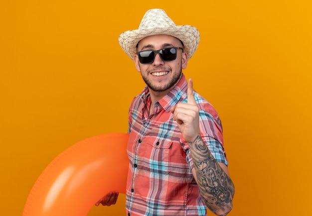 Homem jovem viajante caucasiano sorridente com chapéu de praia de palha em óculos de sol segurando um anel de natação e apontando para cima isolado na parede laranja com espaço de cópia