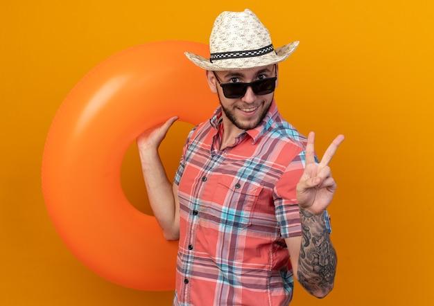 Homem jovem viajante caucasiano sorridente com chapéu de praia de palha em óculos de sol segurando um anel de natação e gesticulando o sinal da vitória isolado em um fundo laranja com espaço de cópia