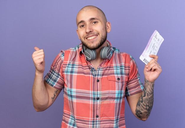 Homem jovem viajante caucasiano sorridente com fones de ouvido ao redor do pescoço, segurando a passagem aérea e manuseando isolado no fundo roxo com espaço de cópia