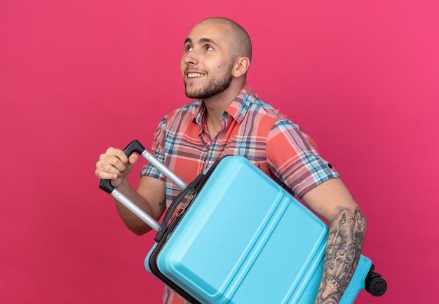 Homem jovem viajante caucasiano sorridente segurando mala olhando para cima isolado no fundo rosa com espaço de cópia