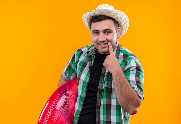 Homem jovem viajante com camisa xadrez e chapéu de verão segurando um anel inflável apontando com o dedo para seu sorriso em pé sobre a parede laranja