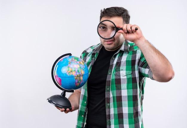 Homem jovem viajante com camisa xadrez segurando um globo através da lupa em pé sobre uma parede branca