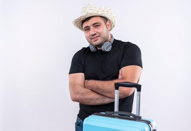Homem jovem viajante com camiseta preta e chapéu de verão com mala de pé e braços cruzados, parecendo confiante sobre a parede branca