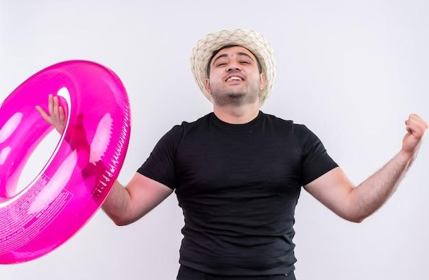 Homem jovem viajante com camiseta preta e chapéu de verão segurando um anel inflável e cerrando os punhos, regozijando-se com seu sucesso em pé sobre uma parede branca