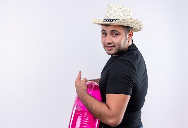 Homem jovem viajante com camiseta preta e chapéu de verão segurando um anel inflável, parecendo confiante, apontando com o dedo para o lado em pé sobre uma parede branca