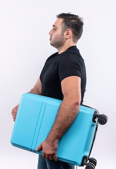Homem jovem viajante com camiseta preta segurando mala de pé de lado com cara séria na parede branca
