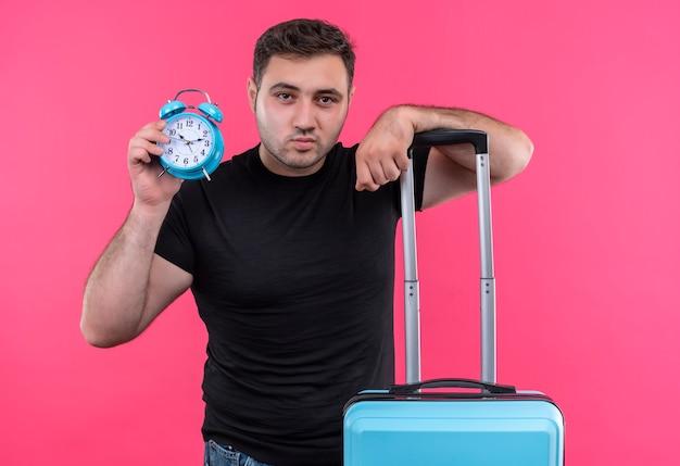 Homem jovem viajante com camiseta preta segurando mala e despertador com expressão séria e confiante em pé sobre a parede rosa