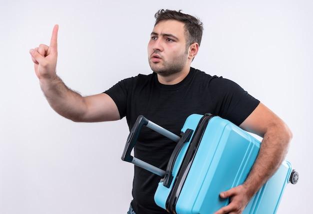 Homem jovem viajante com camiseta preta segurando mala e gesticulando para esperar um minuto com a mão olhando com expressão séria em pé sobre a parede branca