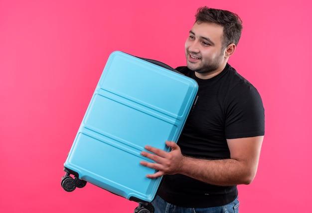 Homem jovem viajante com camiseta preta segurando mala olhando para o lado e sorrindo com uma cara feliz em pé sobre a parede rosa