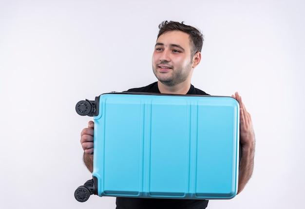 Homem jovem viajante com camiseta preta segurando mala olhando para o lado sorrindo com uma cara feliz em pé sobre a parede branca