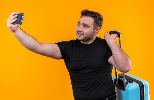 Homem jovem viajante com camiseta preta segurando mala tirando selfie, usando seu smartphone sorrindo para a câmera em pé sobre a parede laranja