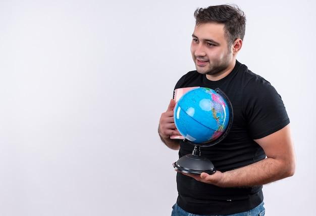 Homem jovem viajante com camiseta preta segurando um globo olhando para o lado com um sorriso no rosto em pé sobre uma parede branca