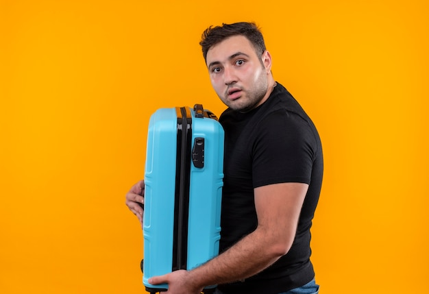 Homem jovem viajante com camiseta preta segurando uma mala assustado em pé sobre a parede laranja