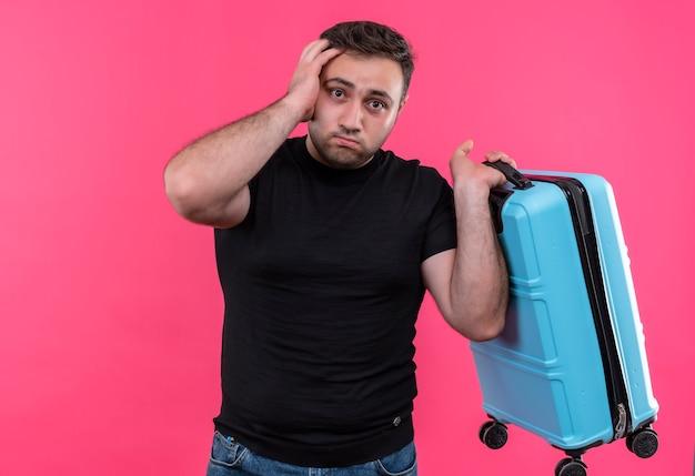 Homem jovem viajante com camiseta preta segurando uma mala, confuso e muito ansioso em pé sobre a parede rosa