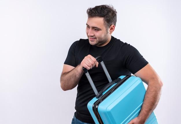 Homem jovem viajante com camiseta preta segurando uma mala, olhando de lado, sorrindo, positivo e feliz em pé sobre uma parede branca