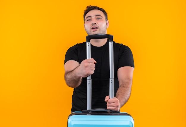 Homem jovem viajante com camiseta preta segurando uma mala, parecendo confiante, pronto para as férias em pé sobre a parede laranja