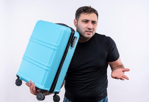 Homem jovem viajante com camiseta preta segurando uma mala, parecendo de lado confuso e muito ansioso em pé sobre uma parede branca