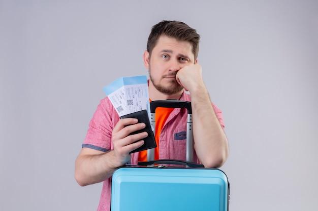 Homem jovem viajante com chapéu de verão segurando passagens aéreas e mala, olhando para a câmera, cansado e entediado em pé sobre um fundo branco isolado