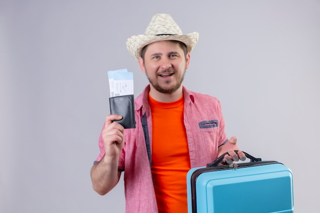 Homem jovem viajante com chapéu de verão segurando passagens aéreas e mala olhando para a câmera, sorrindo com uma cara feliz em pé sobre um fundo branco isolado