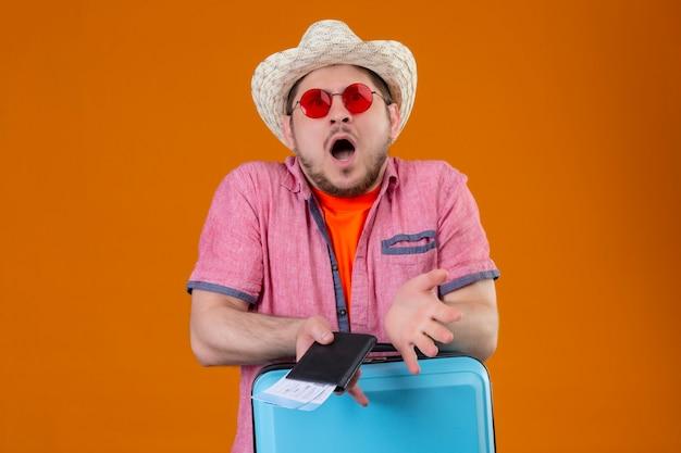 Homem jovem viajante com chapéu de verão usando óculos escuros segurando uma mala e passagens aéreas, olhando para a câmera espantado e surpreso em pé sobre um fundo laranja