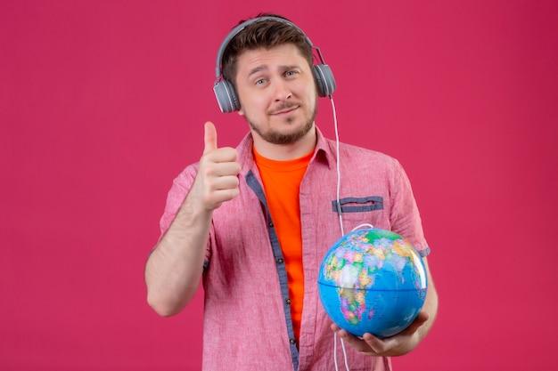Homem jovem viajante com fones de ouvido, ouvindo música, segurando um globo, mostrando os polegares para cima, sorrindo em pé sobre um fundo rosa