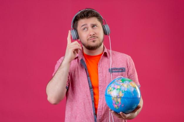 Homem jovem viajante com fones de ouvido segurando um globo, ouvindo música, sorrindo positivamente em pé sobre o fundo rosa