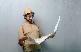Homem jovem viajante com um mapa e bolsa de couro