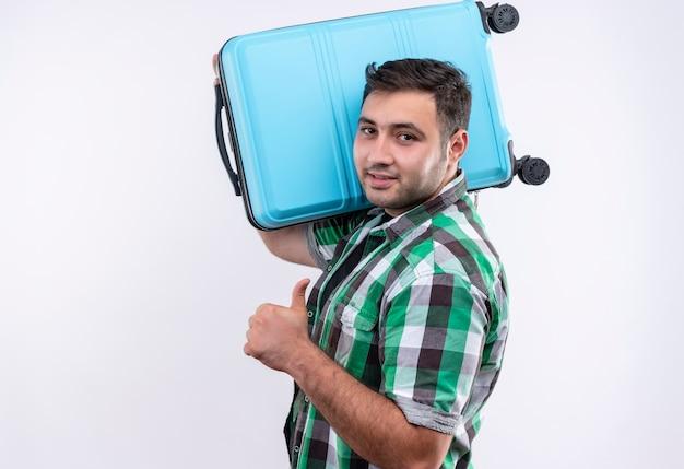 Homem jovem viajante de camisa xadrez segurando uma mala mostrando os polegares sorrindo confiante em pé sobre uma parede branca