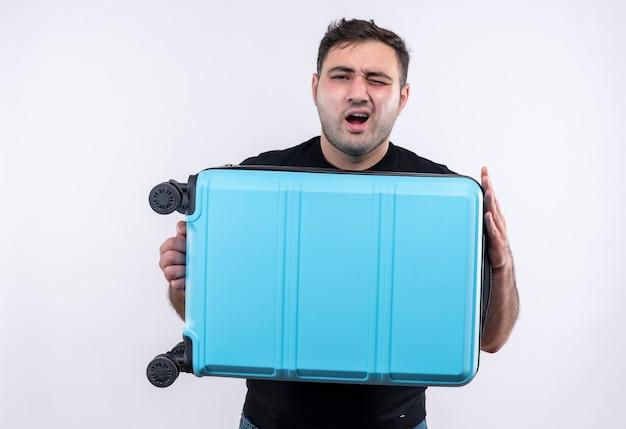 Homem jovem viajante de camiseta preta segurando uma mala e gritando com expressão irritada em pé sobre uma parede branca