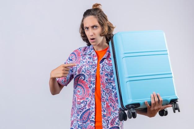 Homem jovem viajante descontente com mala apontando com o dedo para ele olhando confuso em pé