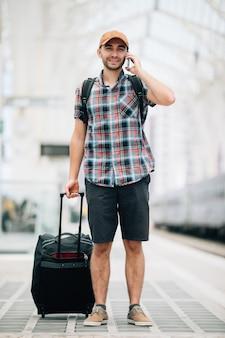 Homem jovem viajante falando ao telefone na estação de trem