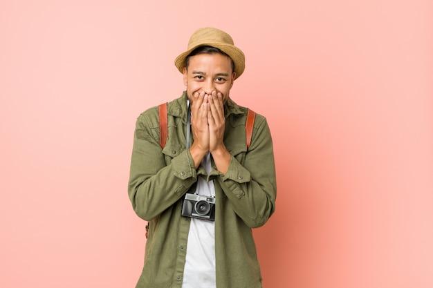 Homem jovem viajante filipino rindo de algo, cobrindo a boca com as mãos.