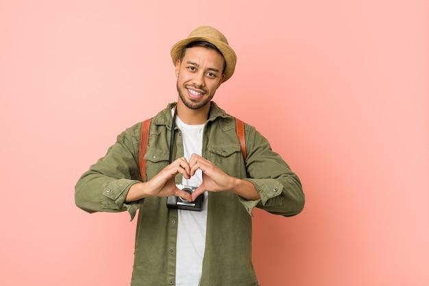Homem jovem viajante filipino sorrindo e mostrando uma forma de coração com as mãos.