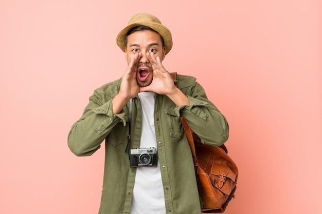 Homem jovem viajante gritando animado para a frente.