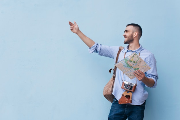 Homem jovem viajante mostrando algo segurando um mapa em pé contra um fundo azul