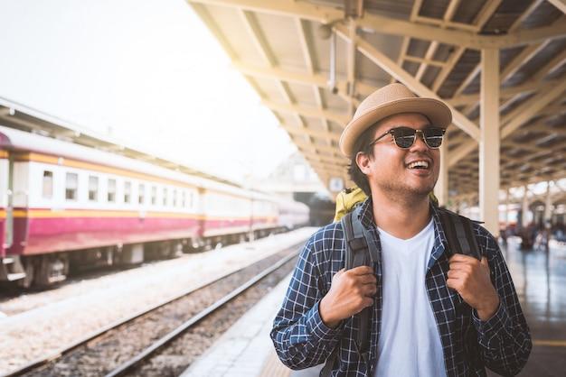 Homem jovem viajante na estação de trem de plataforma. conceito de viagem.