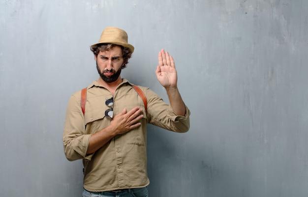 Homem jovem viajante ou turista sorrindo com confiança ao fazer uma promessa sincera ou juramento