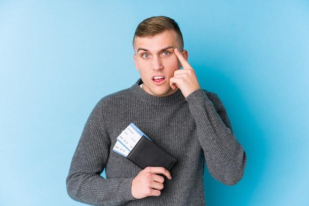 Homem jovem viajante segurando um cartão de embarque, mostrando um gesto de decepção com o dedo indicador