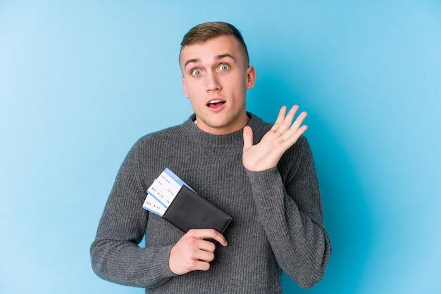 Homem jovem viajante segurando um cartão de embarque surpreso e chocado.