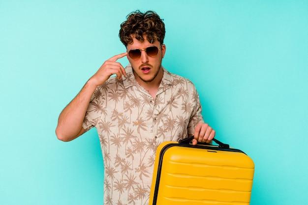Homem jovem viajante segurando uma mala amarela sobre fundo azul, mostrando um gesto de decepção com o dedo indicador.