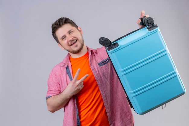 Homem jovem viajante segurando uma mala azul, olhando para a câmera, sorrindo alegremente, positivo e feliz, mostrando o número dois ou o sinal da vitória em pé sobre um fundo branco