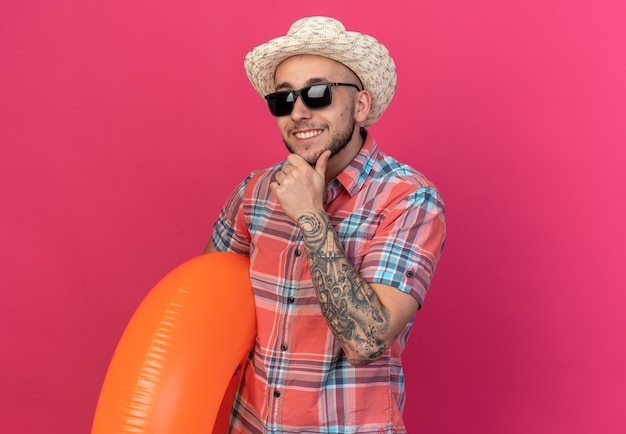 Homem jovem viajante sorridente com chapéu de palha de praia em óculos de sol, colocando a mão no queixo e segurando anel de natação isolado na parede rosa com espaço de cópia